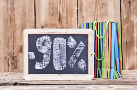ninety percent discount written on blackboard with colorful shoping bag  photo