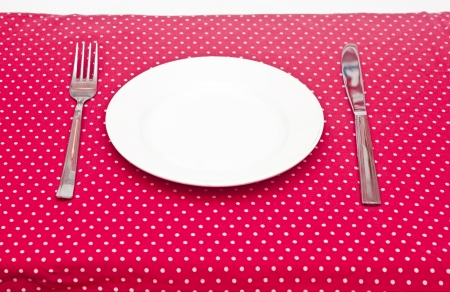 Empty white dinner plate with utensils on fun red polka dot tablecloth. photo