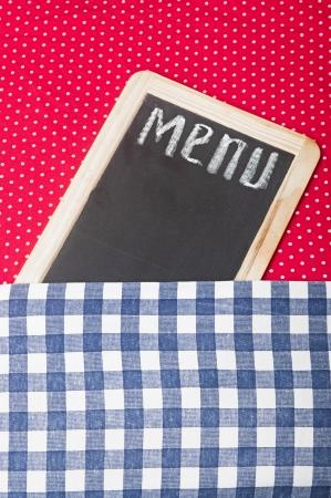 blankness: Menu title written with chalk on blackboard lying on tablecloth red polka dot