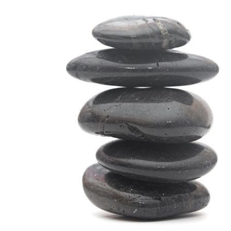 Black massage stones stacked, isolated on white  photo