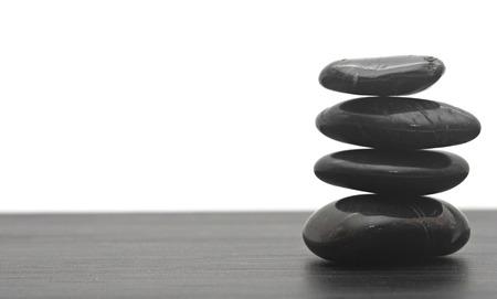 Black massage stones stacked, isolated.  photo