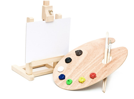 Wooden easel with clean paper and wooden artists palette loaded with various colour paints and brush, isolated on a white background photo
