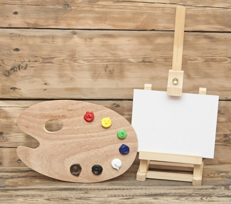 Wooden easel with clean paper and artist color palette photo