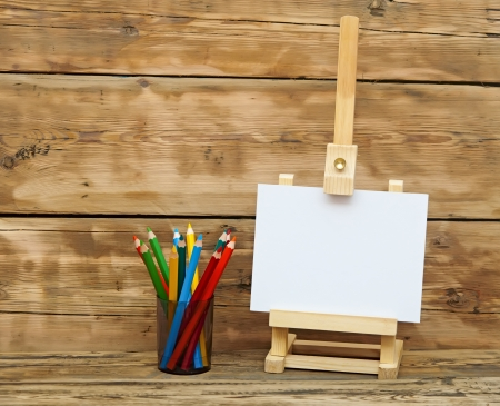 Wooden easel with clean paper and colorful pencils photo