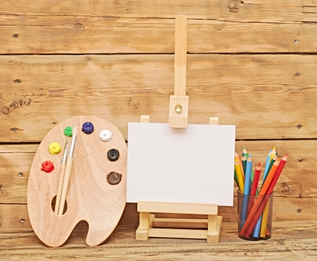 Wooden easel with clean paper and wooden artists palette loaded with various colorful paints and  pencils againt wooden background  photo