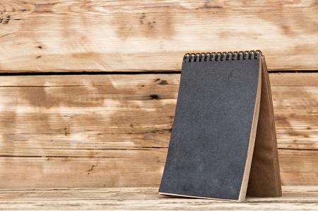 Single blank desk calendar on wooden table photo
