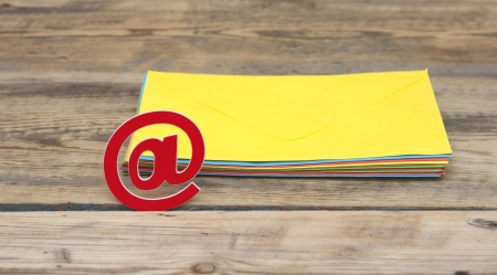 E-mail symbol and pile colorful envelopes on old wooden background  photo