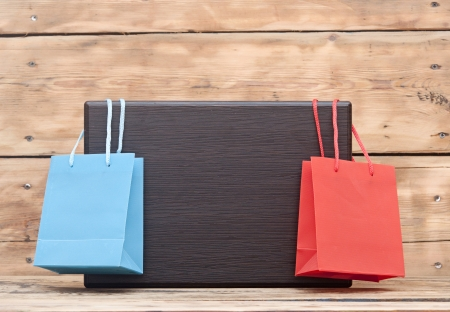 colorful shopping bags hanging on blank wood plate with copy space for your text photo