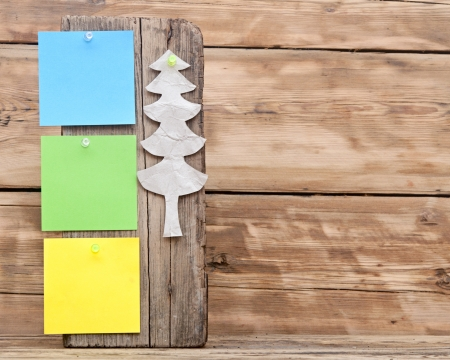 colorful reminder notes attached on a old wooden signboard with paper christmas tree photo