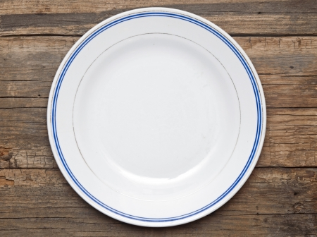Empty white plate on old wooden table