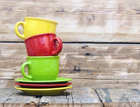 Colorful coffee cups on wooden table photo