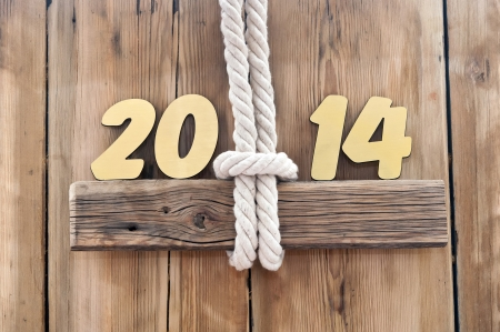 2014 year golden figures hanging by rope on wooden sign  photo