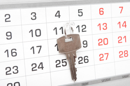 A house key on a calendar background, paying your mortgage on time  photo