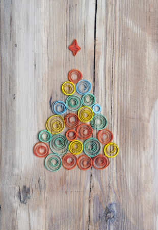Christmas tree made of paper on wood background photo