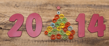 word 2014 and curling paper Christmas tree on wood background photo