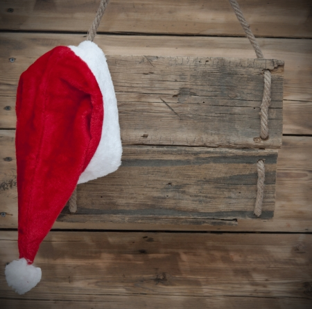 Weathered wooden sign with Santa hat photo