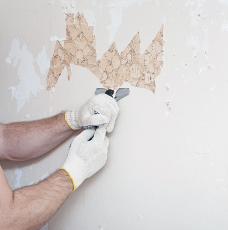 upholster: Hand removing wallpaper from wall  Stock Photo