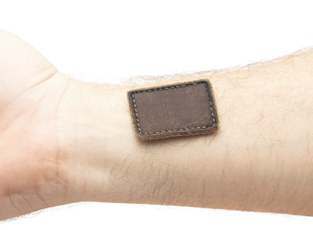 leather label: Blank leather label sewed on a hand isolated over white Stock Photo