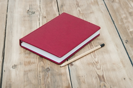 red leather note book with pencil on wood background photo