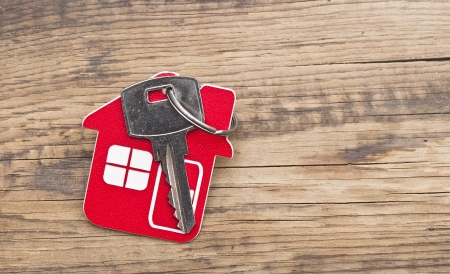 mortgage: Symbol of the house with silver key on wooden background  Stock Photo