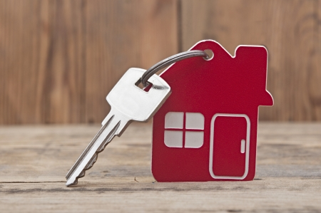 Symbol of the house with silver key on wooden background  Stockfoto