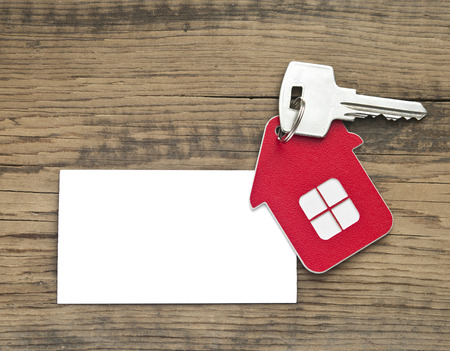 Key with house icon and blank paper on wooden