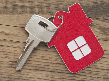 house mortgage: A key in a lock with house icon on it  Stock Photo