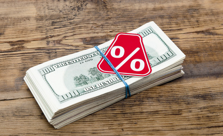 discounting: Sign % on the background of one hundred dollar bills