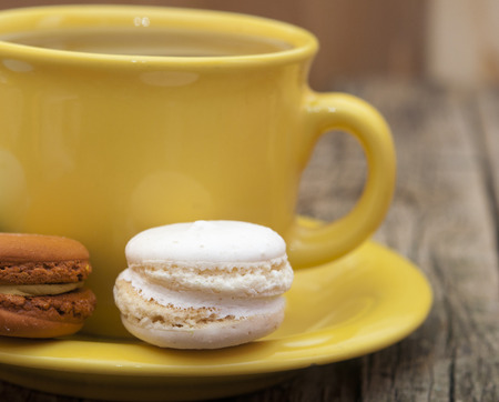 colorful macaroon with a cup of coffee on old wooden background  photo