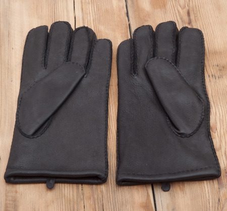 table top: Pair of mens black leather gloves on wooden table top