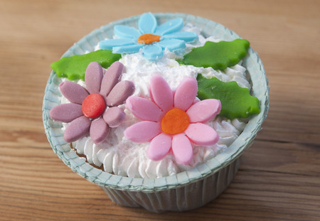 beautiful muffins decorated with spring flower on vintage wooden background photo