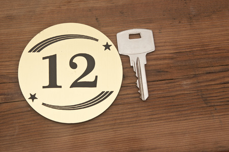 number 12: Hotel suite key with room number 12 on wood table  Stock Photo