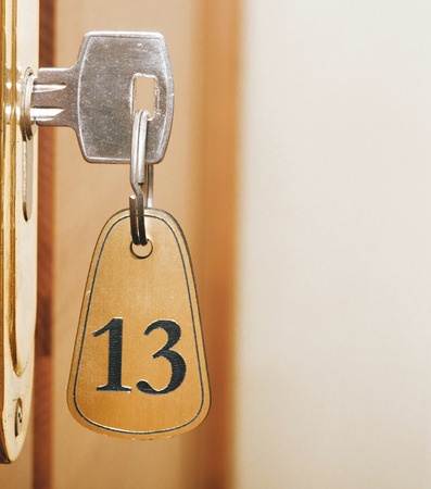 Closeup of an old keyhole of room number 13 with key on a wooden door photo