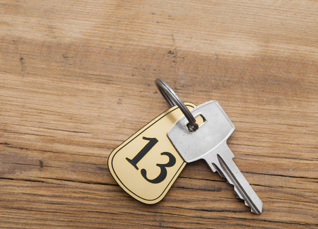 Closeup of an key of room number 13 with key on a wooden desk photo