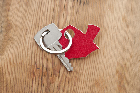 Symbol of the house with silver key on vintage wooden background photo