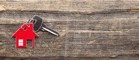 Symbol of the house with silver key on vintage wooden background