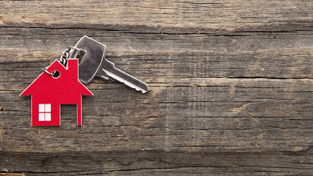 Symbol domu se stříbrným klíčem na vinobraní dřevěné pozadí Reklamní fotografie