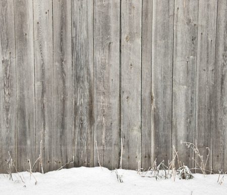 Frozen old wooden fence in snow photo