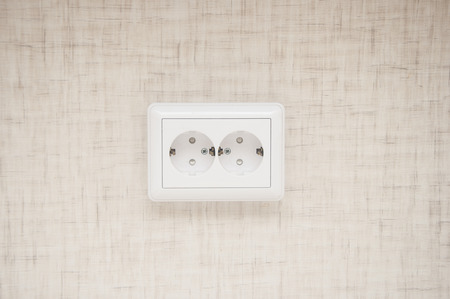 White electric socket on the wall. Close up