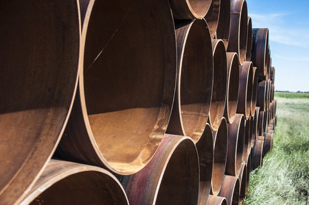 rusting: closeup of a pile of large and rusting steel pipes