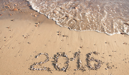 orthographic symbol: 2016 written in sand on sunny beach