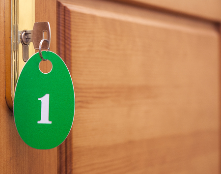 view of a wooden doorway: Door handles on wood wing of door and key in keyhole with numbered label Stock Photo