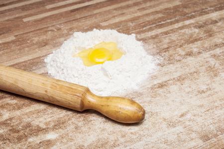 haciendo pan: Huevo quebrado en la harina, los medios para hacer pan