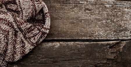tog: Handmade knitted wool scarf on wooden background Stock Photo