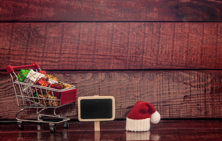 profit celebration: Shopping cart full of colorful gift boxes and blank sign over wooden background Stock Photo