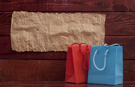 soft sell: colorful  paper shopping bag on wooden table Stock Photo