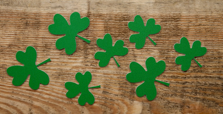 three leafed: Green clovers or shamrocks on rustic wood background Stock Photo