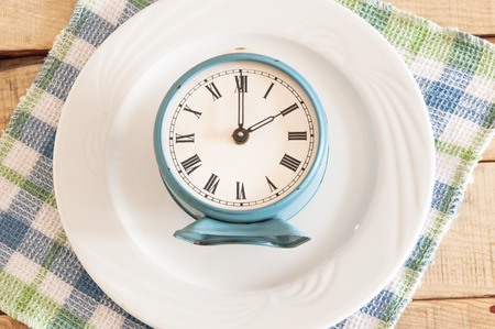 antique dishes: Meal time table place setting with alarm clock Stock Photo