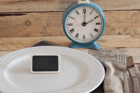 meal time: Meal time table place setting with alarm clock Stock Photo