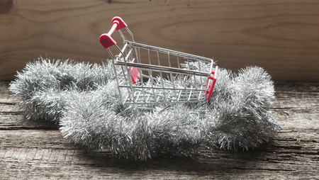 Shopping cart and new-year tinsel Stock Photo